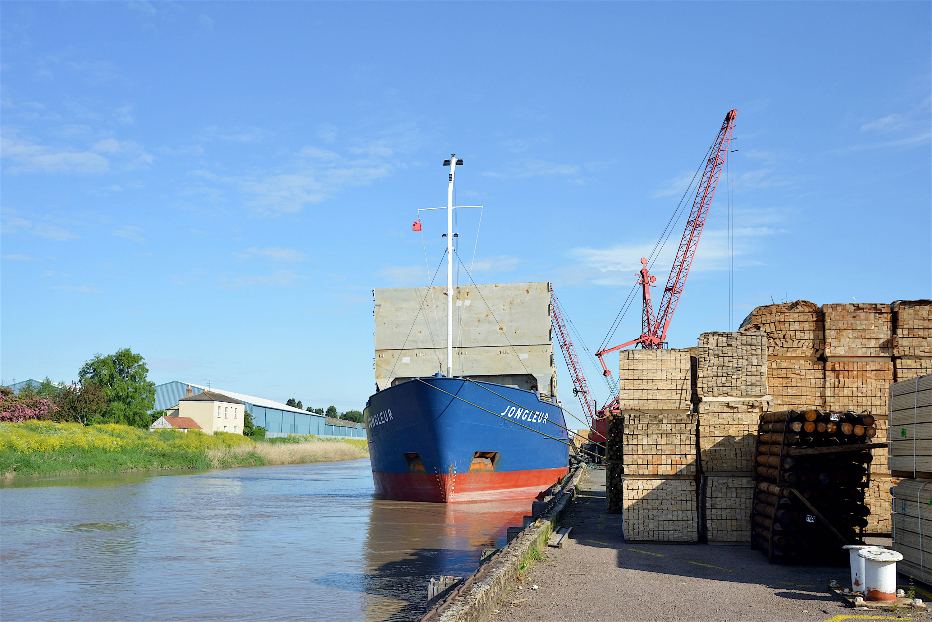 vessel at dock of Port of Wisbech with stacks of timber